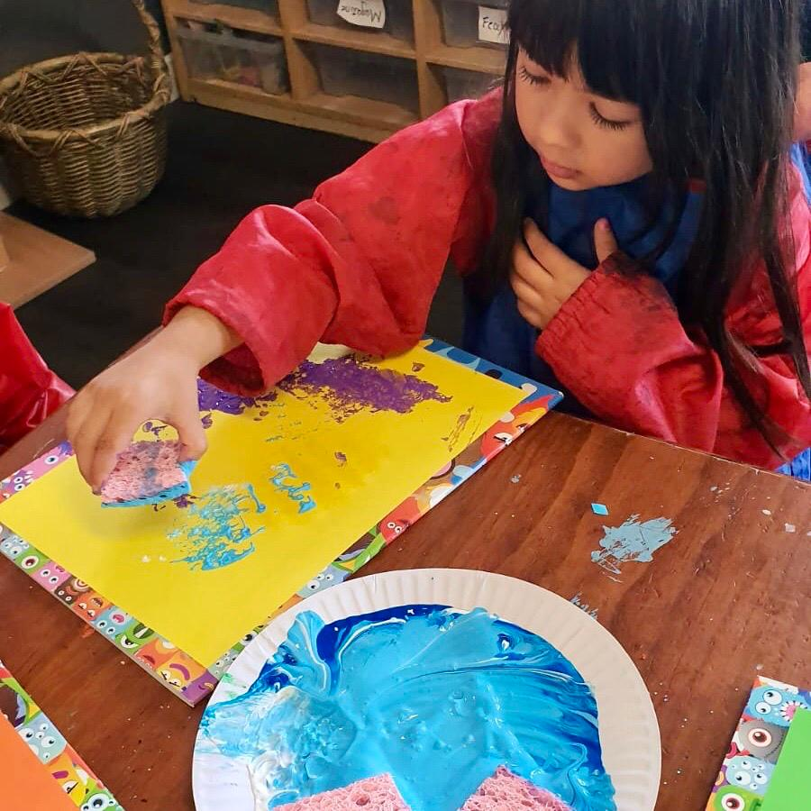 Girl learning how to paint at Inspira Kids preschool